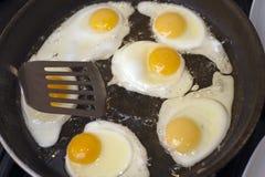 Steka en gruppering av ägg Arkivbild