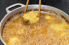 Steka fisken i en panna med kokande olja Royaltyfri Foto