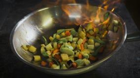 steka grönsaker för kock Cognac antändas i pannan Öppna brand i köket lager videofilmer