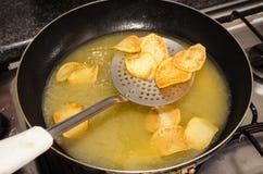 Steka rundade potatisar på en svart panna med kokande olja Arkivbilder
