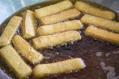 Steka tofuen med varm olja i en stor panna asiatisk mat Arkivbilder