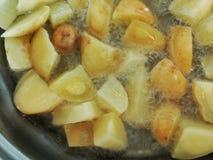Steka unga potatisar i varm olja Fotografering för Bildbyråer