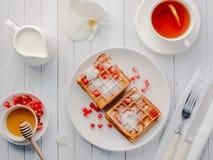 Steken de heerlijke mond-water gevende Weense wafels met honing en granaatappelzaden op een witte plaat, houten achtergrond aan Stock Fotografie