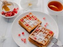 Steken de heerlijke mond-water gevende Weense wafels met honing en granaatappelzaden op een witte plaat, houten achtergrond aan Royalty-vrije Stock Foto's