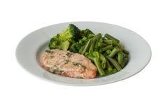 Stekfisk med gröna grönsaker på en isolerad vit platta Royaltyfri Fotografi