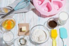 Stekhet bakgrund med ingredienserna av mjölet är ägget av keroben, äggen, smöret och redskapen I mitten Royaltyfri Foto