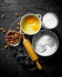 Stekhet bakgrund Mjöl med mjölkar, mandlar och former för stekheta kakor royaltyfria foton