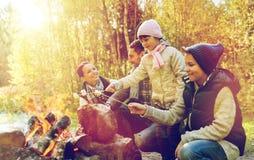 Stekhet marshmallow för lycklig familj över lägereld Arkivbild