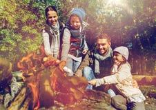 Stekhet marshmallow för lycklig familj över lägereld Royaltyfri Fotografi