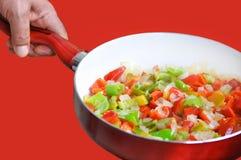Stekhet panna med grönsaker. Rött och paprikor och lökar som isoleras på röd bakgrund. Arkivfoto