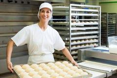 Stekheta brödrullar för kvinnlig bagare royaltyfri fotografi