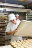 Stekheta brödrullar för kvinnlig bagare arkivbild