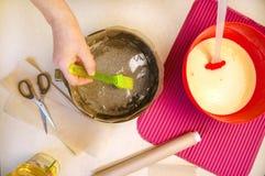 Stekheta ingredienser och redskap för att laga mat sockerkakan Kvinnan smörjer olja den stekheta maträtten Lekmanna- bästa sikt f Royaltyfri Fotografi
