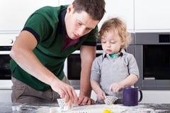 Stekheta kakor för fader med sonen royaltyfri fotografi
