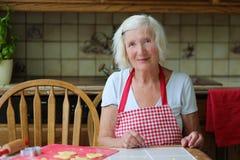 Stekheta kakor för lycklig hög kvinna i köket Royaltyfri Foto