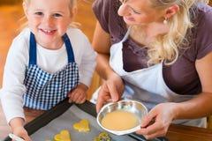 Stekheta kakor för moder och för dotter tillsammans fotografering för bildbyråer