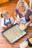Stekheta kakor för moder och för dotter tillsammans royaltyfri bild