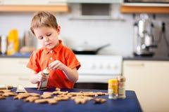 Stekheta kakor för pojke arkivbild