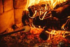 Stekheta marshmallower vid branden Hemtrevligt chalethem med firepla Arkivfoton