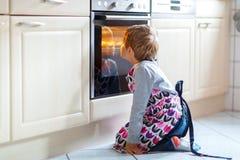Stekheta muffin för rolig blond ungepojke inomhus Arkivbilder