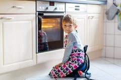 Stekheta muffin för rolig blond ungepojke inomhus Royaltyfria Foton