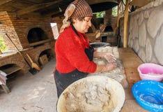 Stekheta pajer för hög kvinna i henne hem- kök i georgisk bystil med stenugnen Royaltyfria Bilder