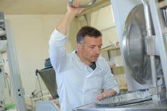 Stekhett bagettbröd för stolt bagare i kök Arkivbild