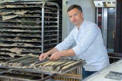 Stekhett bagettbröd för stolt bagare i kök arkivbilder