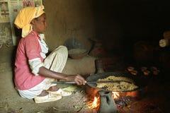 Stekhett korn för etiopisk kvinna på wood brand royaltyfria bilder