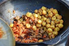 Stekkött och potatisar som lagas mat i en stor frilufts- kokkärl royaltyfri foto