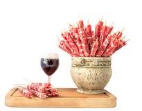 Steknålar av kött och ett exponeringsglas av rött vin Arkivfoton