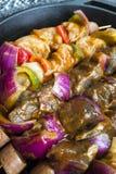 Steknålar av köttkorven och grönsaker i stekpanna arkivbilder