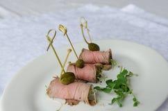Steknålar för köttrullar med kapris på den vita plattan Royaltyfri Foto