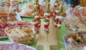 Steknålar med gröna oliv för tomatmozzarellaen och mer foods gillar royaltyfri fotografi