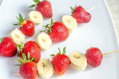 Steknålar med jordgubbar och bananen arkivbilder