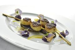 Steknålen för fiskmaträtten av kammusslor täckte med en skorpa med svarta ris och lilor Royaltyfri Bild