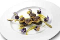 Steknålen för fiskmaträtten av kammusslor täckte med en skorpa med svarta ris och lilor Royaltyfria Foton