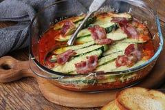 Stekpanna med den stekte tomater, zucchinin, ost och örter på träskärbräda Fotografering för Bildbyråer