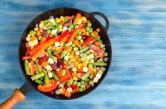 Stekpanna med djupfrysta grönsaker på blå bakgrund fotografering för bildbyråer