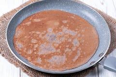 Stekpanna med smakliga tunna pannkakor på tabellen arkivfoton