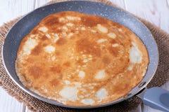 Stekpanna med smakliga tunna pannkakor på tabellen arkivbild