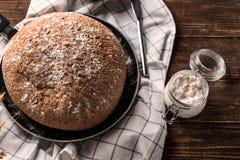 Stekpanna med smakligt nytt bröd och kruset av mjöl på trätabellen arkivbilder
