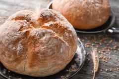Stekpanna med smakligt nytt bröd på trätabellen, closeup arkivbild