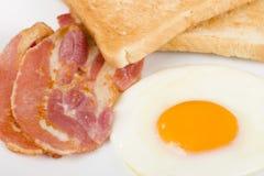 Stekt ägg, bacon & rostat bröd. Arkivfoton