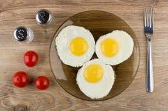Stekt ägg i brun platta, salt, peppar, tomater och gaffel Royaltyfria Bilder
