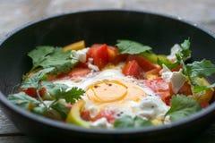 Stekt ägg i en panna med tomater och gräsplaner Arkivbild