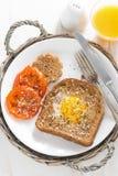 stekt ägg i ett rostat bröd, stekte tomater och orange fruktsaft Fotografering för Bildbyråer