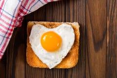 Stekt ägg i form av en hjärta Arkivbilder