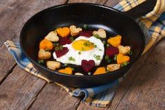 Stekt ägg i formhjärta och hjärtor, morötter, beta och potatisar Arkivbild