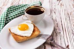 Stekt ägg med rostat bröd på en platta arkivbilder